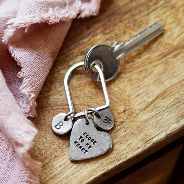 """Heart keyring with """"close to my heart"""" inscribed on attached to a key"""