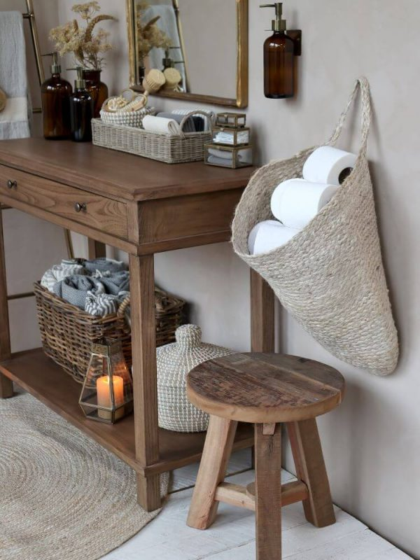 Basket hanging holding toilet rolls within a bathroom setting