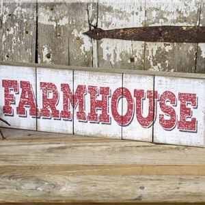 """Wooden rustic rectangle sign with a whitewashed background and the word """"Farmhouse"""" printed on it in red block print"""