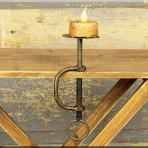 A metal candle stick that is clamped to the side of a table with a candle to show how it functions