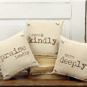 2 small natural coloured cushions with a message printed on each