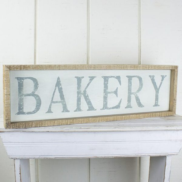 """Wooden framed rectangle sign with white background and the words """"BAKERY"""" printed in a grey colour"""