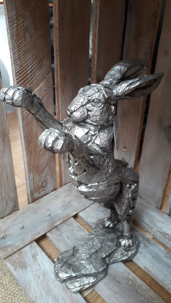 A textered silver solid hare standing up on its hind legs with its front paws raised