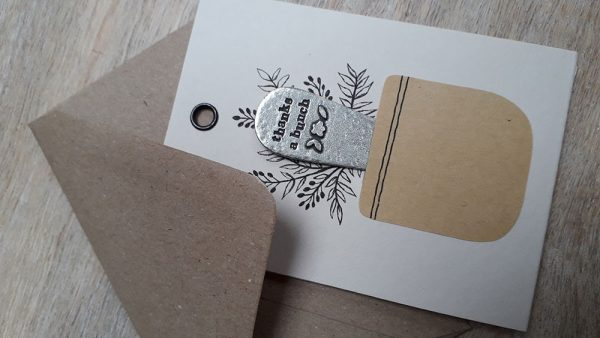 """A card with a vase on it with which serves as a pocket. Black ink flowers are drawn from the plant pot. Within the plant pot sits a metal plant marker with """"thanks a bunch"""" imprinted on it."""