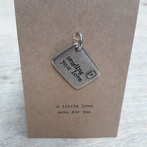 """A small envelope shaped token with """"sending you love"""" imprinted on it"""