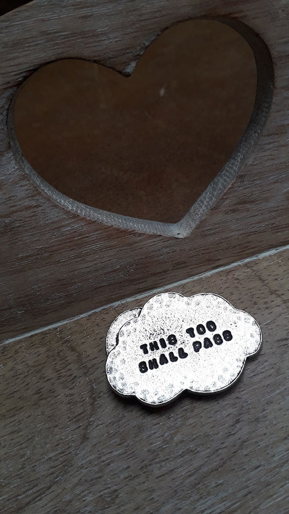 """Cloud shaped token with the words """"this too shall pass"""" on one side and a sun breaking through the cloud on the other"""