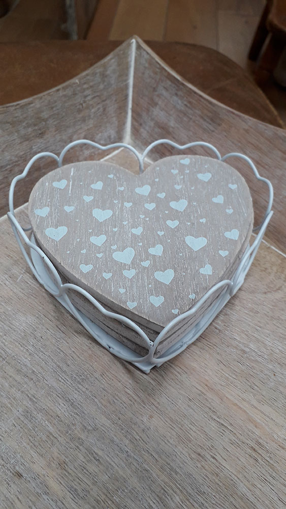 4 wooden heart shaped coasters with white hearts on sitting within a metal heart shaped coaster holder