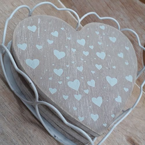 four wooden coasters with white hearts on sitting in a white metal heart shaped coaster holder