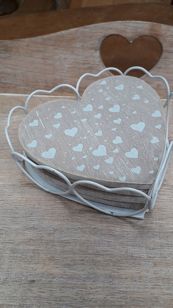 White metal heart shaped coaster holder with 4 wooden heart shaped coasters included with white hearts of differing sizes dotted on