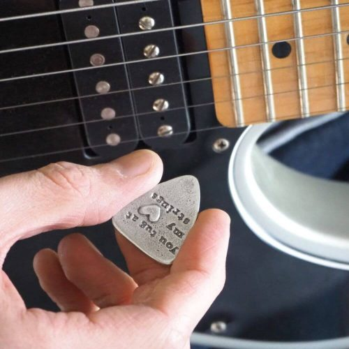 Guitar plectrum being held and ready to use to play guitar