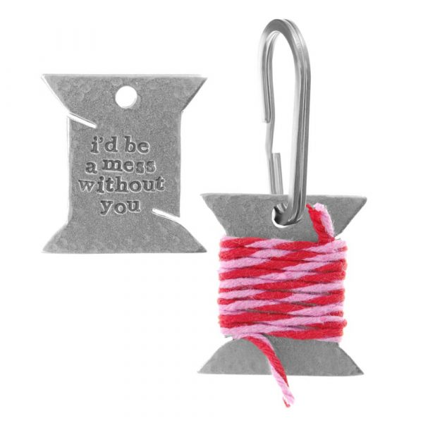 """Keyring showing it entwinded with the pink and red thread and then it unravelled with the wording """"i'd be a mess without you"""" inscribed on it"""