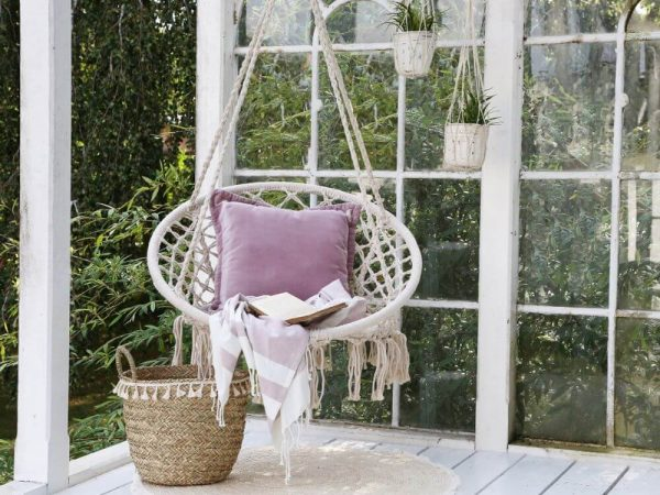 Swing chair displayed, hanging with cushions and throws