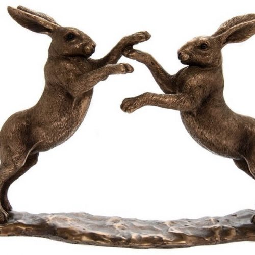 Tow bronzed hares on their hind legs with front legs in a fighting position