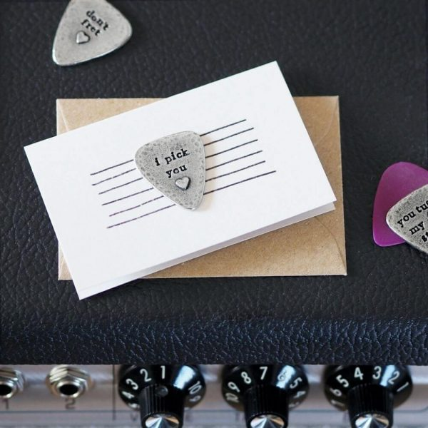 """Guitar plecturm with the words """"i pick you"""" and a picture of a heart on. The plectrum is attached to a small card with an envelope"""