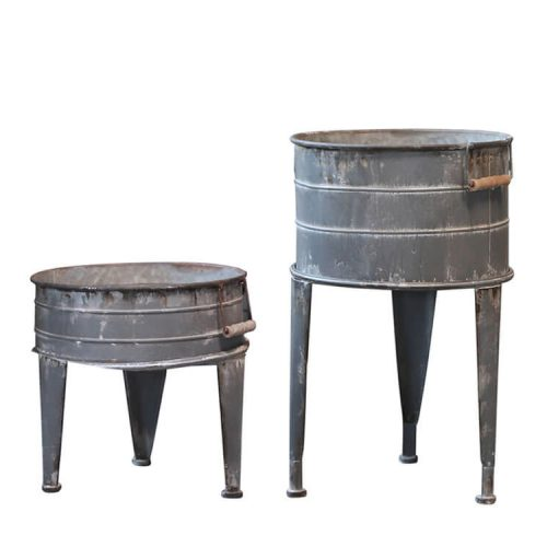 Two matching but different sized metal planters on feet