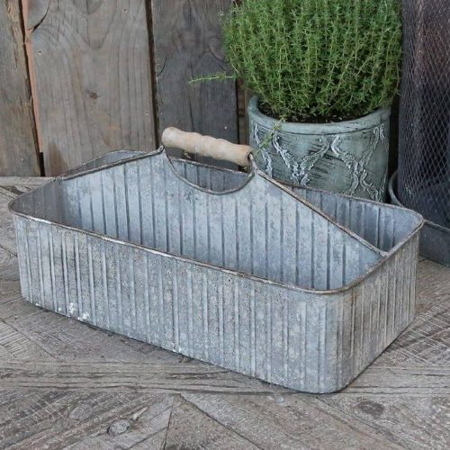 Metal caddy with a compartment either side and a carrying handle in the middle