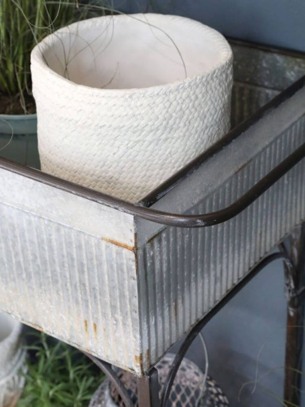 Metal planter with white plant pot sitting in it