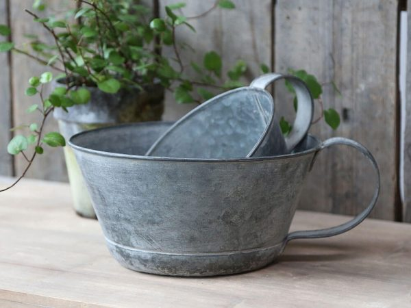 Two metal saucer type bowls with large handles to one side
