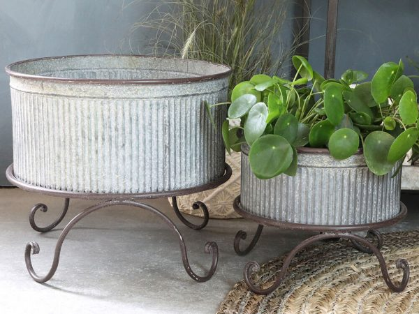 A ribbed metal round planter with a white splattered look. It stands on twirled metal feet.
