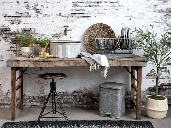 A display of a wooden table with rustic items incorporated including the dish drainer