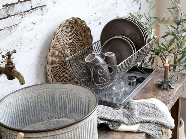 A display of a sink area with dish drainer and dishes on show