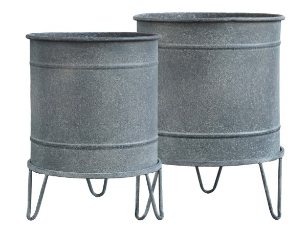 Two rough looking metal planters standing on hairpin feet