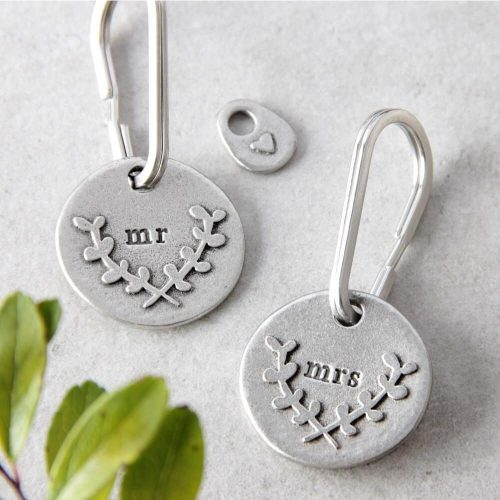 """two keyrings with """"mr"""" and """"mrs"""" inscribed on them"""