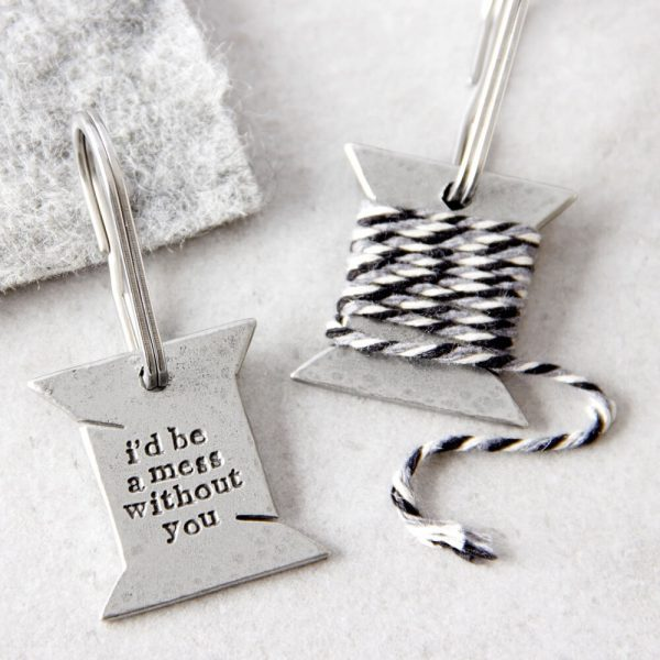 """Keyring entwinded with black, grey and white thread with the wordimg """"i'd be a mess without you"""" revealed when unraveled"""