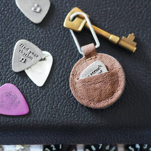 Brown leather keyring pouch displaying the holding of a guitar plectrum