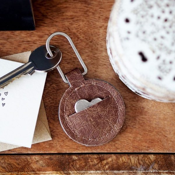 Brown leather circle disc with a pouch within it attached to a keyring to attach keys to