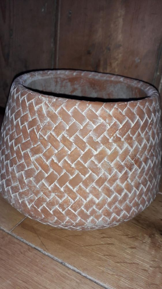 A terracotta coloured plant pot with a basket weave effect on it