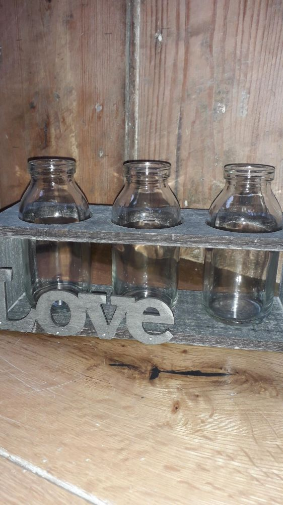 """A wooden box with 3 old fashioned small milk bottles standing. The front has the word """"love"""" across it in a metal looking lettering"""