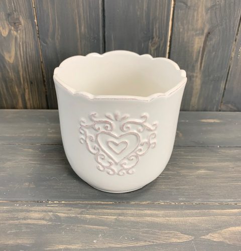 Small white plant pot with a wavered rim and a raised heart design on the front