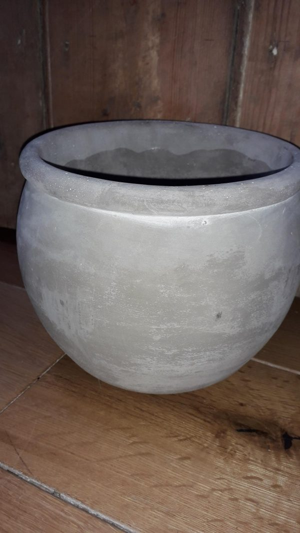 A smooth cement plant pot with a rim around the top