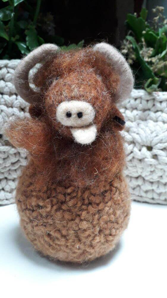 A brown needle felt cow with horns and its tongue sticking out.