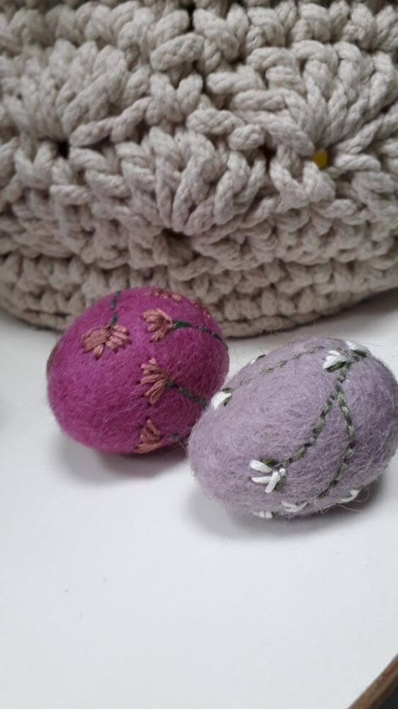 Needle felt eggs of various colours with flower details embroidered on them