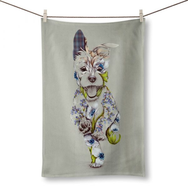 A teatowel with a picture of happy running dog on it. The dog is a patchwork design made up of flowers.