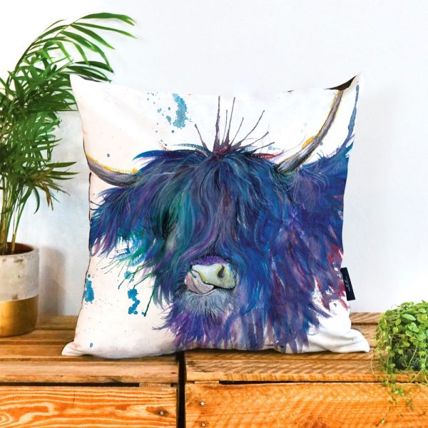 A cushion with a blue highland cow printed on it, The cow has large horns and its tongue is licking its nose