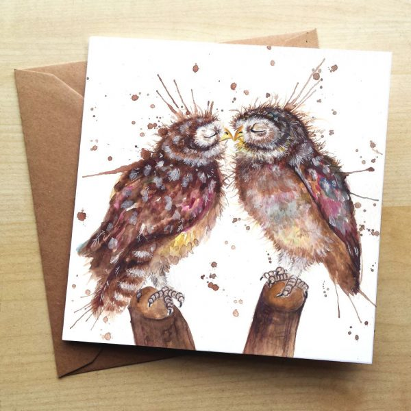 A card with two brown owl perched on a log each facing each other with their eyes closed and their beaks touching to represent them kissing