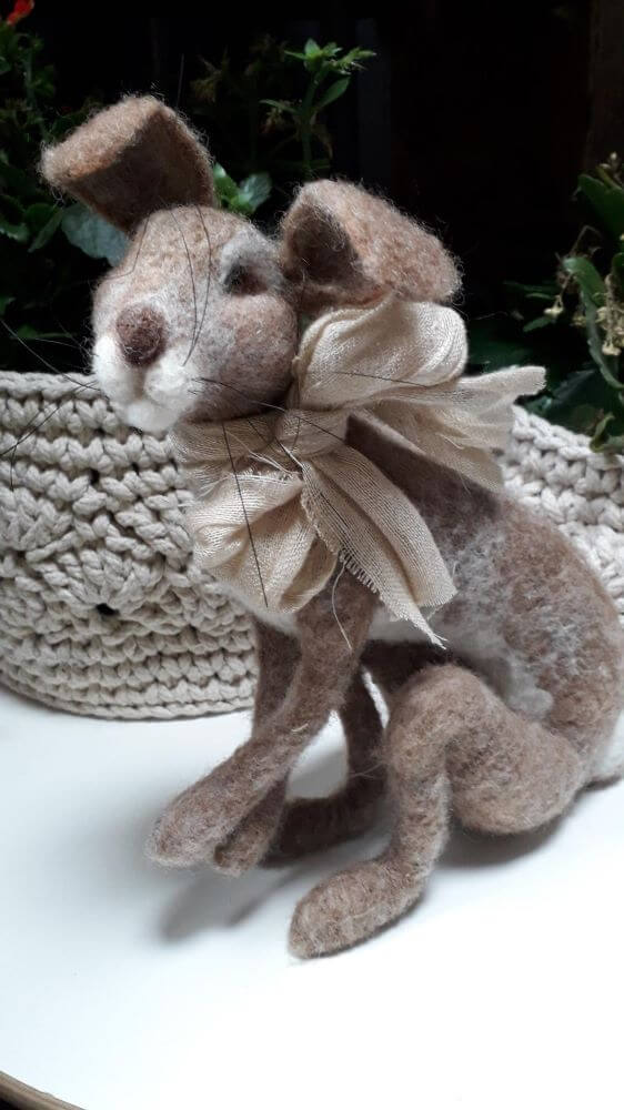 A large needle felt hare in the sitting position with a material bowed scarf around its neck