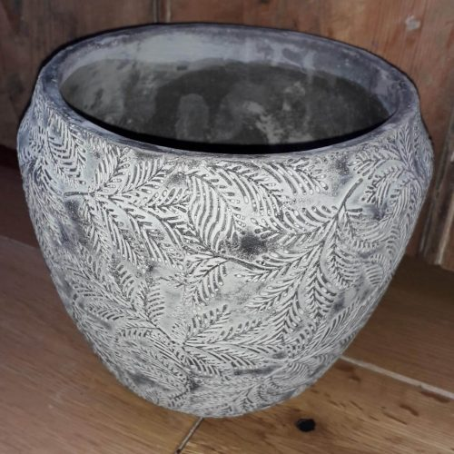 A grey plant pot with leaf pattern in relief