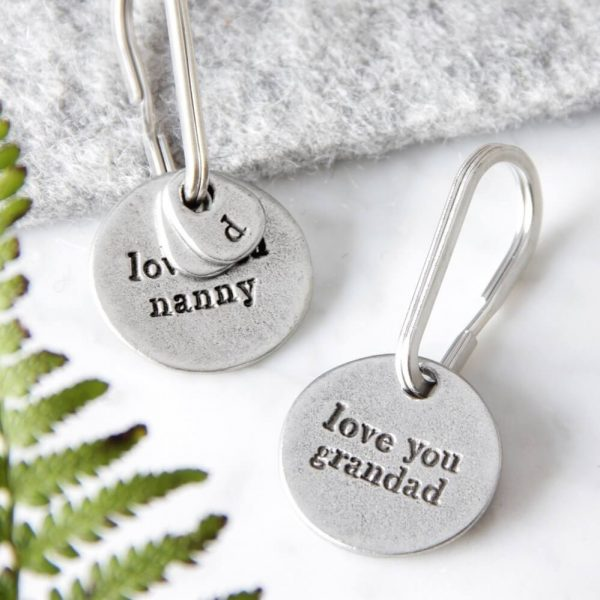 """two round metal keyrings with """"love you nanny"""" and """"love you grandad"""" inscribed on them"""