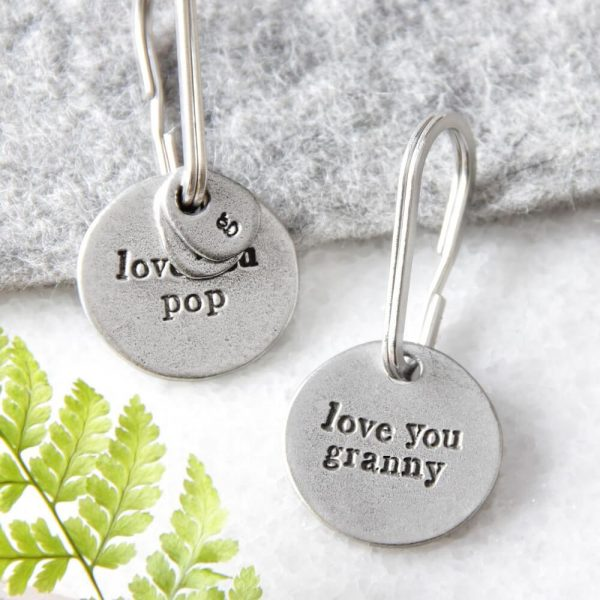 """two round metal keyrings with """"love you pop"""" and """" love you granny"""" inscribed on them"""