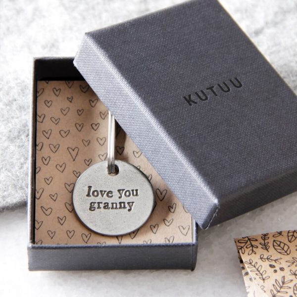 """Round metal keyring displayed in its box with """"love you granny"""" inscribed on it"""