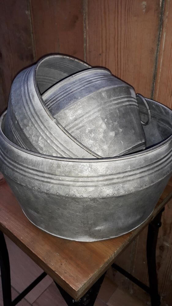 3 metal planters with ringed handles on each side. They are tapered toward the bottom. The top has an indented rim design.