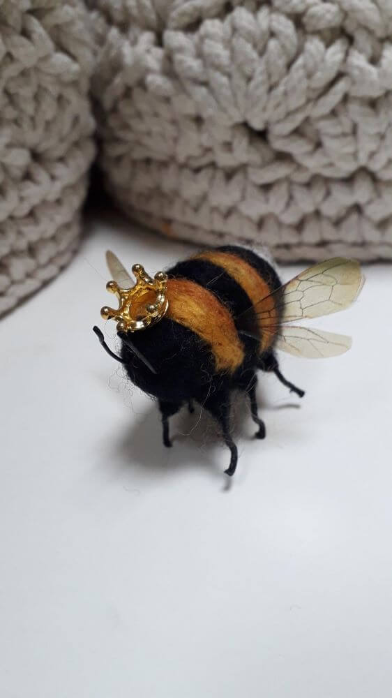 A needle felt bee with a gold crown on its head