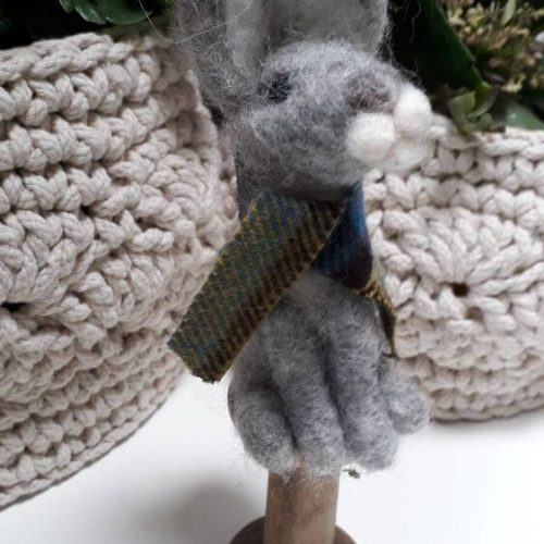 A grey rabbit standing on a bobbin with a green tartan scarf wrapped around its neck