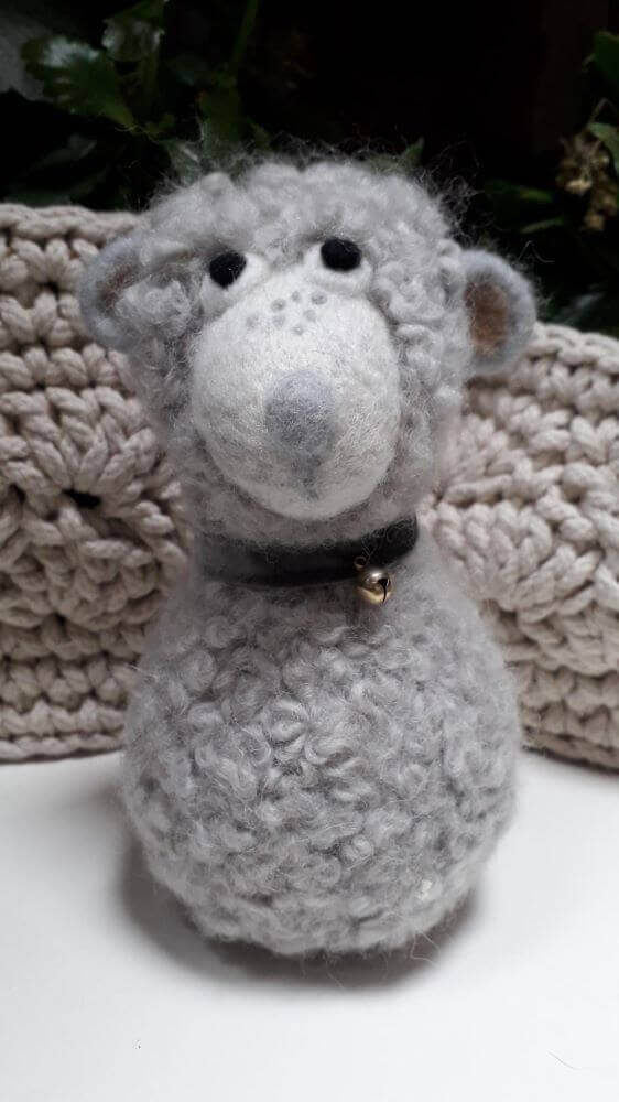 A needle felt white sheep with a collar and bell around its neck