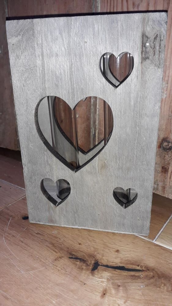 A wooden fascia with a large heart cut out in the middle with smaller heart cut out around the edges. The structure holds test tubes for holding flowers
