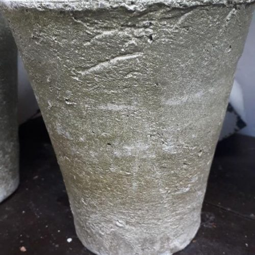 A plantpot that widens at the top. It is a white with rough rustic texture